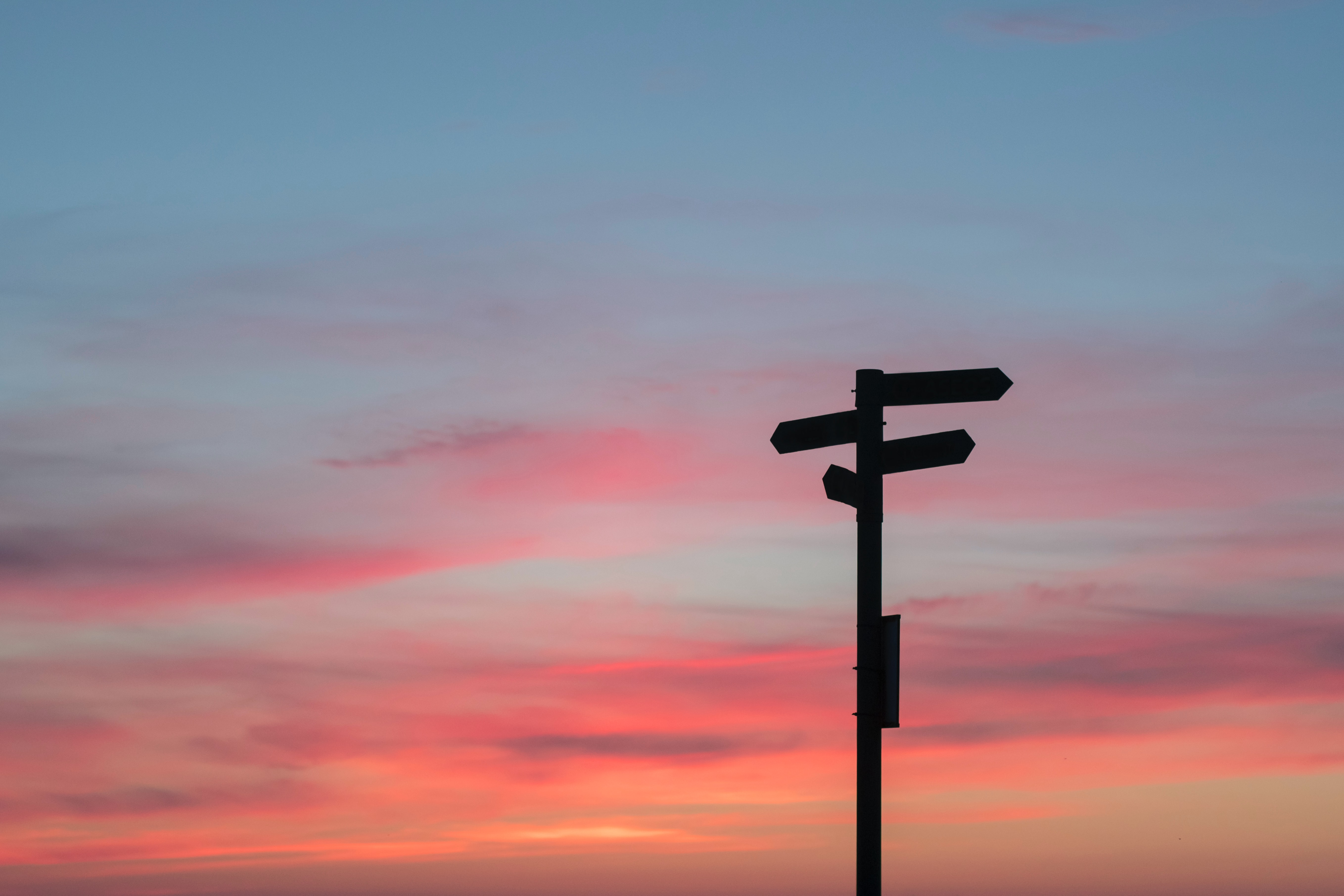 silhouette sign post with sunset or sunrise decisions planning 2021