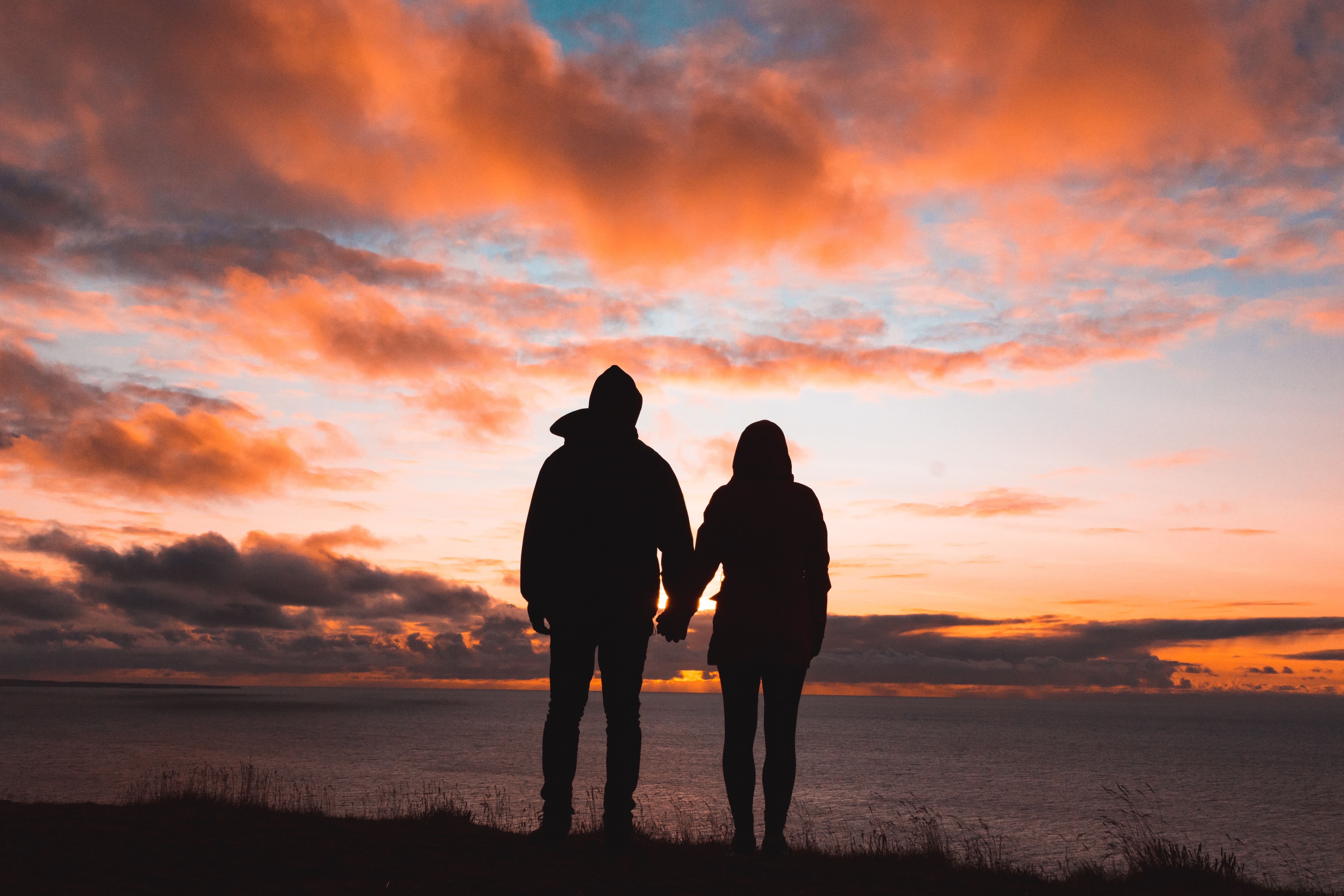 Silhouettes of a couple or partners holding hands with sunset