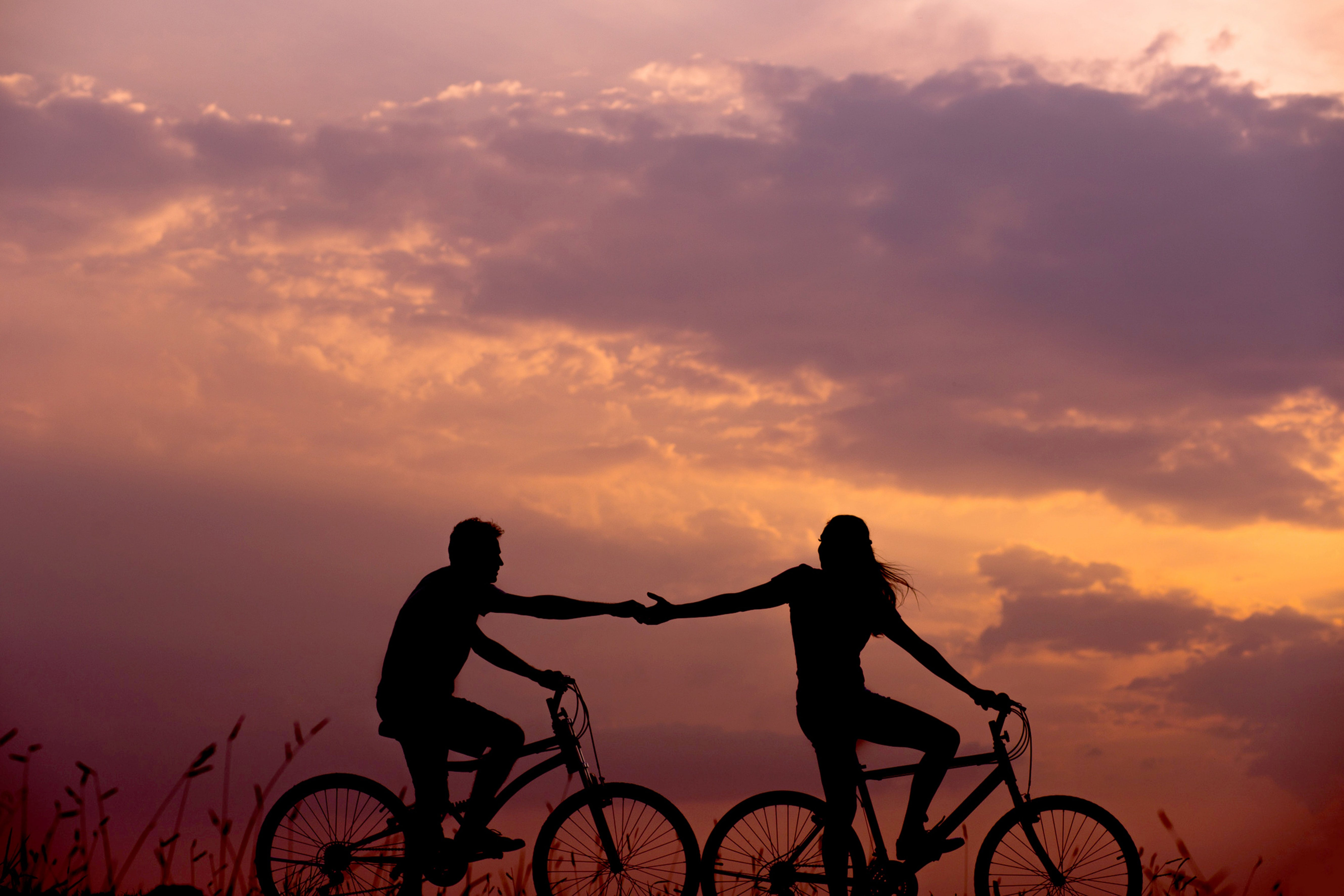 Sunset with couple holding hands while cycling