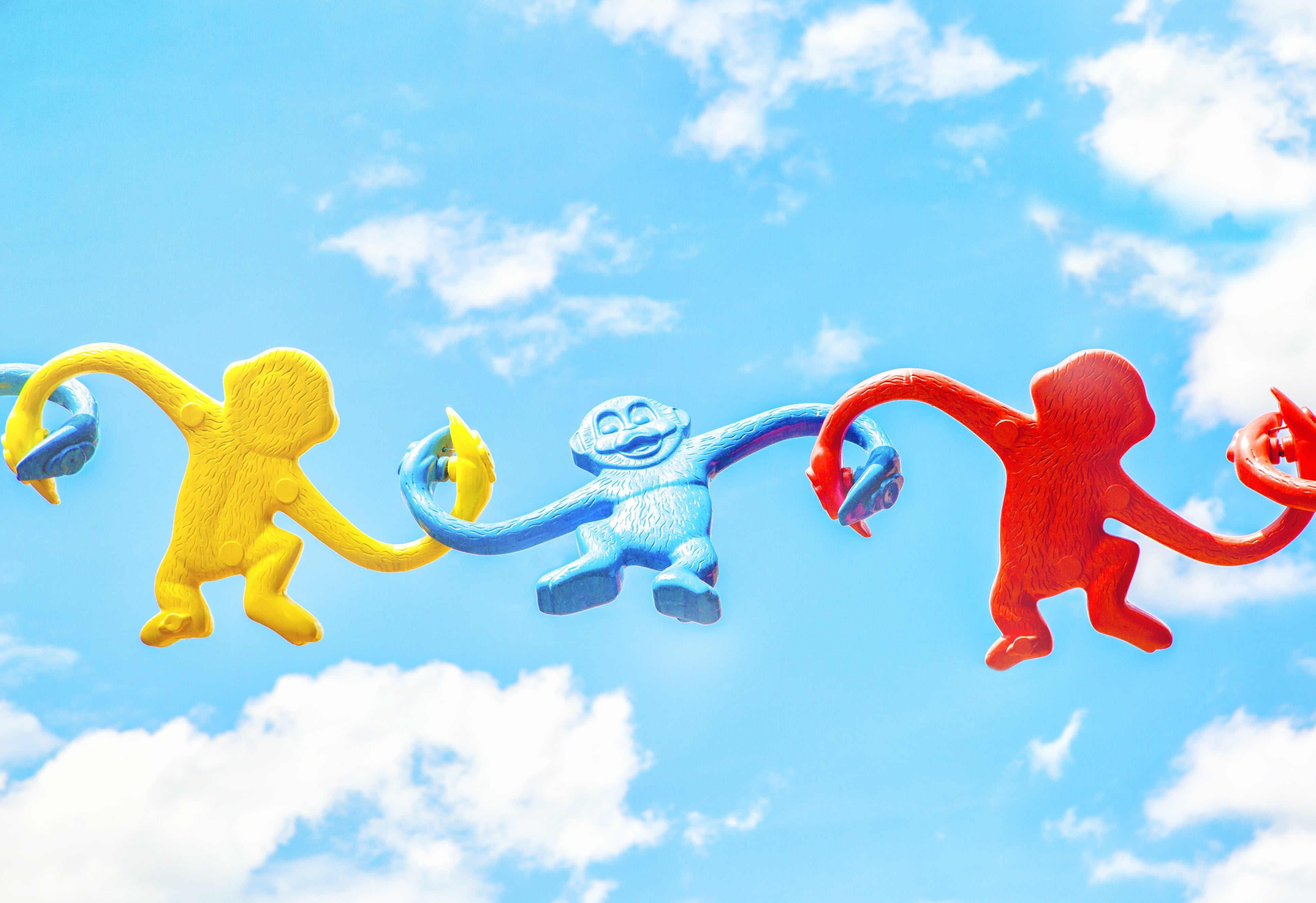 toy monkeys interconnected with blue sky