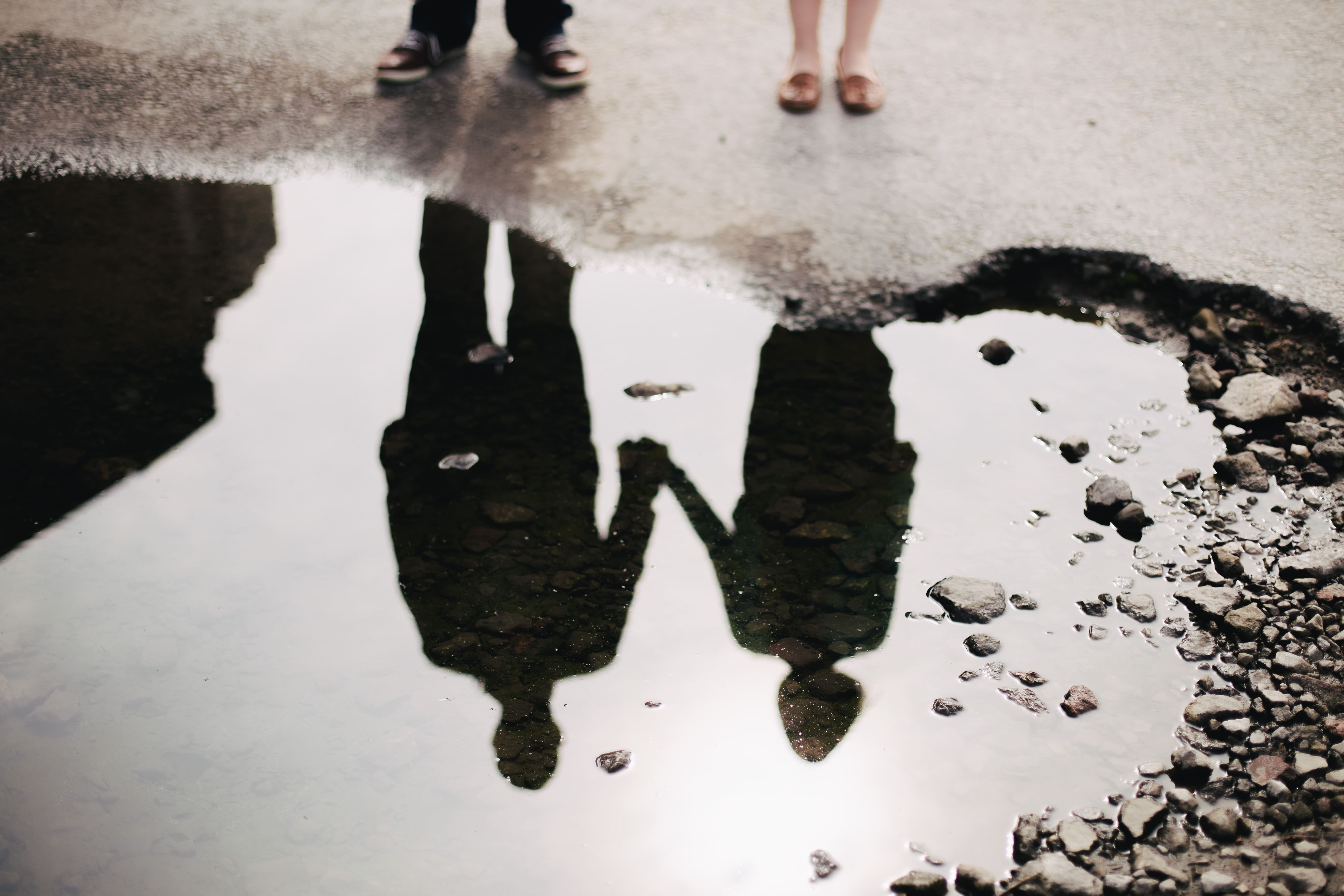 Expat couple reflected in puddle