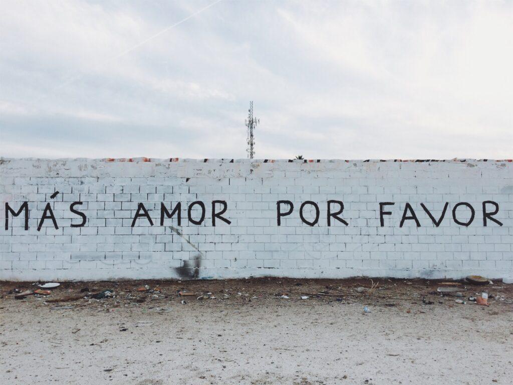 Mas amor por favor more love please written on the wall
