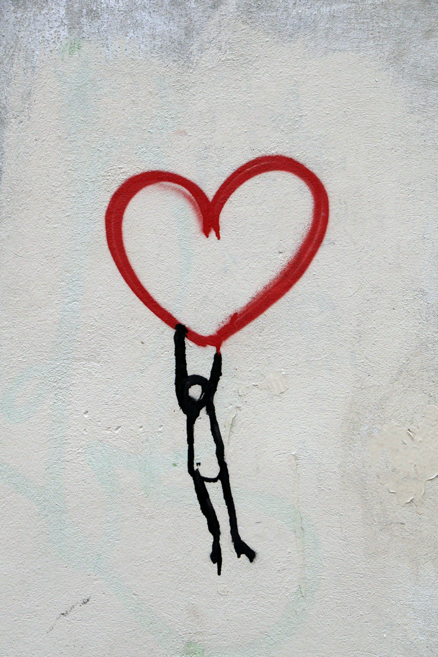 graffiti person being lifted by a red heart self care self love